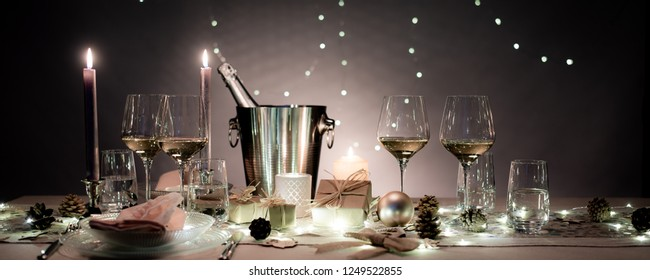 christmas eve party table with white wine glass and glitter season's greeting decoration horizontal header