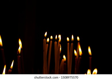 Christmas eve religion service concept picture of candle flame in darkness inside church black background space for copy or text