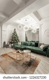 Christmas evening. classic luxurious apartments with decorated christmas tree. Living hall large mirror, green sofa, high windows, columns and stucco.