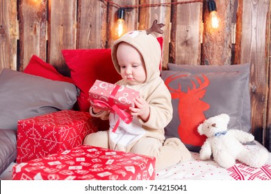 Christmas evening. Little girl sitting and unwraps gifts. coverall-reindeer costume
