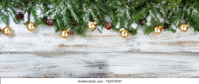 Christmas evergreen branches and golden ornaments on rustic white wood background