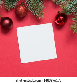 Christmas evergreen branches and red ball on red. View from above, flat lay. Xmas holiday. Template, mockup, greeting New Year card.