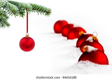 Christmas evergreen spruce tree and red glass balls on snow background