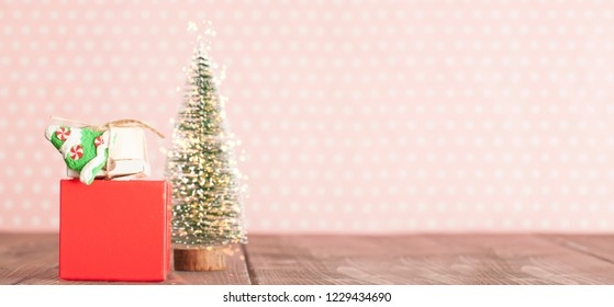 Christmas evergreen tree and gifts on the table in pink nursery room