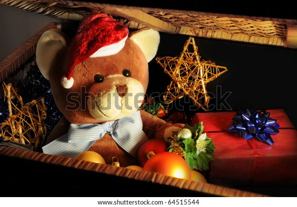 Christmas expectations concept - teddy bear in a dark chest with Christmas decoration and gifts.