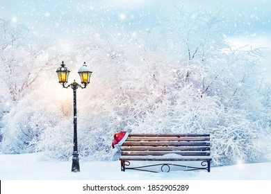 Christmas fabulous image. Lantern, bench and cap of Santa Claus in the winter city park. Winter landscape. - Shutterstock ID 1852905289