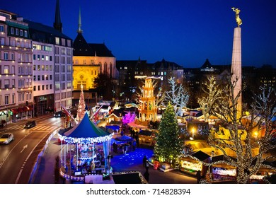 Christmas fair in Luxembourg. Aerial view of traditional Xmas market in old European city center. City decorated for winter holidays. Amusement and shopping for Christmas presents in Europe.