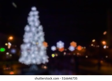 Christmas fair - out-of-focus bokeh background with illuminated snowflakes and christmas tree