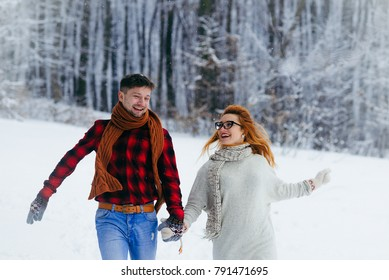 Christmas fairytale. Happy couple is holding hands and cheerfully running along the snowy forest.