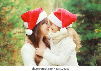 Christmas and family concept - child and mother in santa red hats together