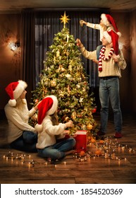 Christmas Family Decorate Xmas tree with Toys. Parents and Kids in Santa Hats together around Fir tree in cozy Living Room Interior, Evening Indoor Lights. Merry Christmas and Happy Holidays! - Shutterstock ID 1854520369