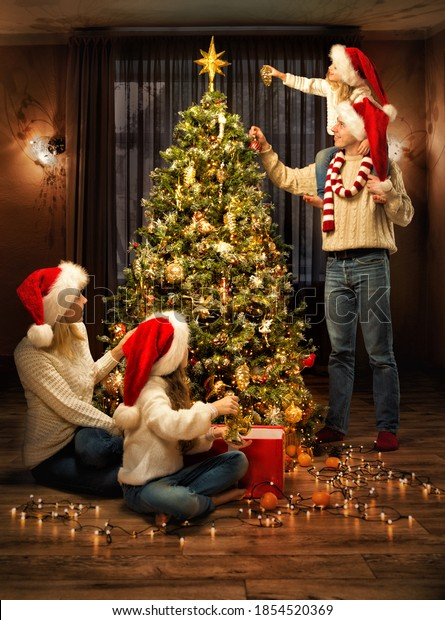 Christmas Family Decorate Xmas tree with Toys. Parents and Kids in Santa Hats together around Fir tree in cozy Living Room Interior, Evening Indoor Lights. Merry Christmas and Happy Holidays!