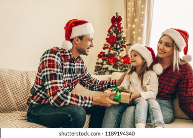 Christmas. Family. Happiness. Dad is giving a present to his daughter who is sitting on her mom's knees. At home near the Christmas tree, all are smiling