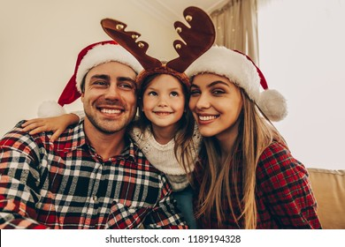 Christmas. Family. Happiness. Dad, mom and daughter in Santa hats are posing at camera and smiling while sitting near the Christmas tree at home
