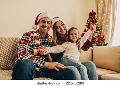 Christmas. Family. Happiness. Dad, mom and daughter in Santa hats sitting on a couch at home near the Christmas tree, all are smiling and looking at camera