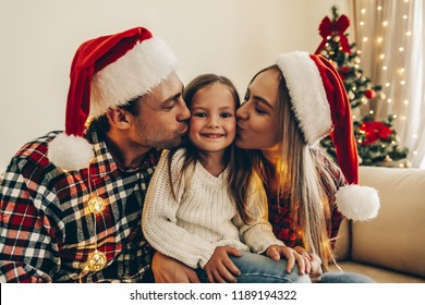 Christmas. Family. Happiness. Parents are kissing her little daughter in Santa hats while sitting on a couch at home near the Christmas tree