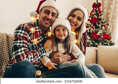 Christmas. Family. Happiness. Portrait of dad, mom and daughter in Santa hats sitting on a couch at home near the Christmas tree, all are smiling