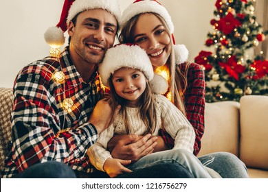 Christmas Family. Happiness. Portrait of dad, mom and daughter in Santa hats sitting on a couch at home near the Christmas tree, all are smiling