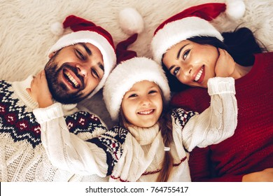 Christmas family! Happy mom,dad and little daughter on Santa Claus hats lying down. Enjoyng love hugs, holidays people. Togetherness concept