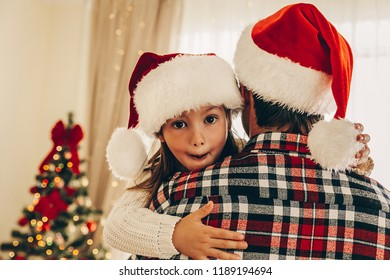 Christmas. Family. Love. Dad is hugging his little daughter while they are spending time near the Christmas tree at home. Both are in Santa hats. Girl is looking at camera