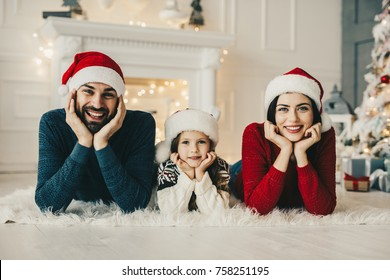 Christmas family. Mom and dad and their little daughter together on home , Enjoing Holidays people