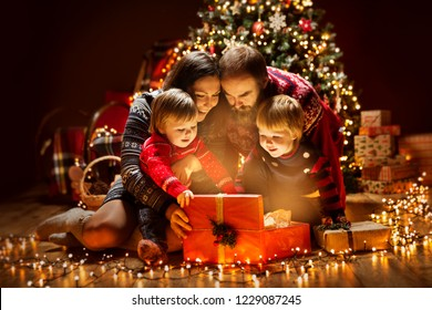 Christmas Family open Lighting Present Gift Box under Xmas Tree, Happy Mother Father Children in Magic Night