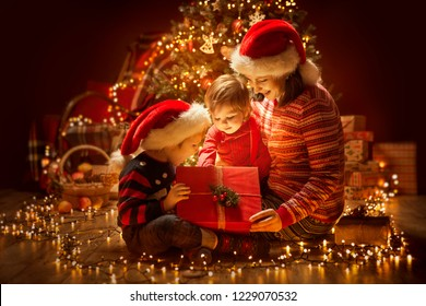 Christmas Family opening Lighting Present Gift Box under Xmas Tree, Happy Mother and Children in Magic Night