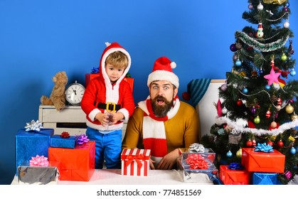 Christmas family opens presents on blue background. Boxing day concept. Santa and little assistant among gift boxes near Christmas tree. Man with beard and son with surprised faces son on New Year eve