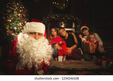 Christmas family portrait in a festive living room with a real Santa Claus.  The atmosphere of celebration and magic.