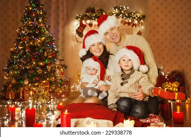 Christmas Family Portrait In Home Holiday Living Room, Kids and Baby at Santa Hat With Present Gift Box, House Decorating By Xmas Tree Candles Garland