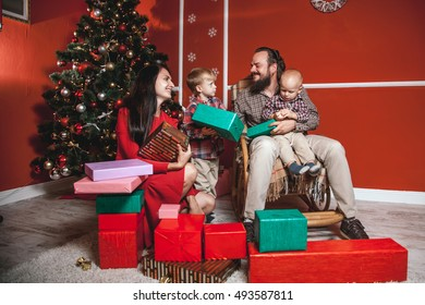 Christmas family portrait in home holiday living room, kids and baby with parents, decorating house with Xmas tree and gifts