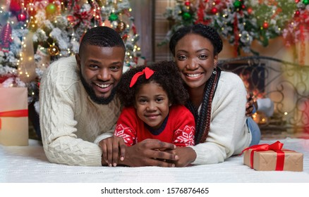 Christmas Family Portrait Near Xmas Tree At Home. Black Father, Mother And Their Little Daughter Celebrating Winter Holidays Together