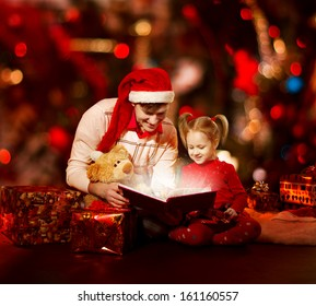 Christmas family reading book. Father and child opening magic fairy tale over red background.