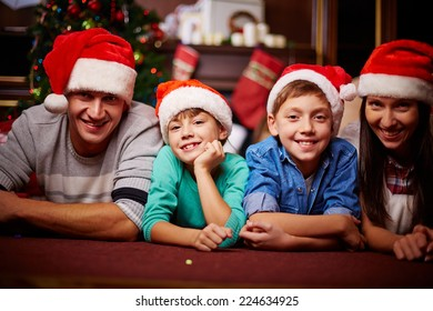 Christmas family in Santa caps looking at camera at home