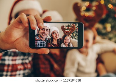 Christmas. Family. Technology. View on the smartphone. Dad, mom and daughter in Santa hats looking at camera and smiling while doing selfie