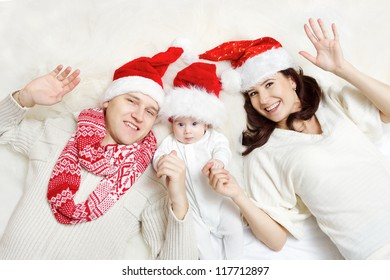 Christmas family of three persons in red hats. Happy parents and small funny baby