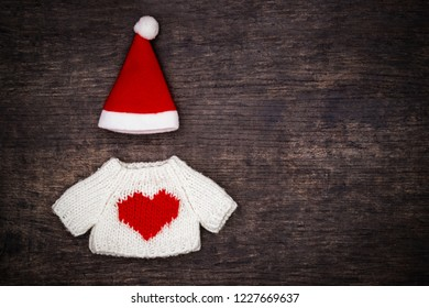 Christmas fashion background with white knitted sweater with red heart and Santa Claus red hat, on brown wooden background, top view, copy space