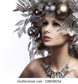 Christmas Fashion Girl with New Year Decorated Hairstyle. Snow Queen. Portrait of Beautiful Young Woman with Silver Christmas Balls