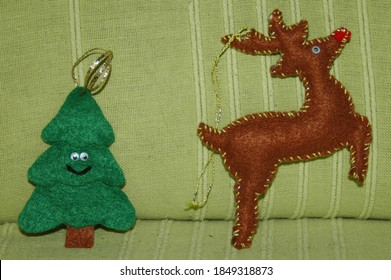 Christmas Felt decorations, unique sweet and handmade. A green smiling tree and a reindeer Rudolph, on a green background