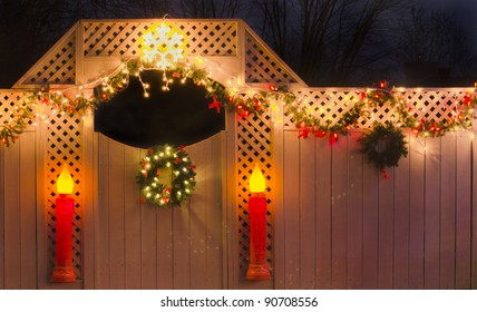 Christmas fence with garland, lights, wreaths and candles.
