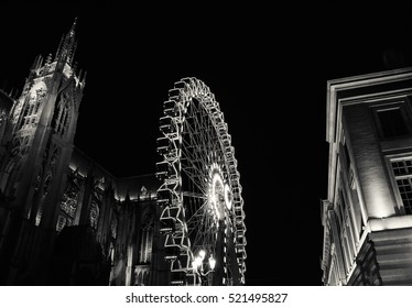 Christmas Ferris wheel in front of the cathedral of Metz. Metz (France). Black and white.