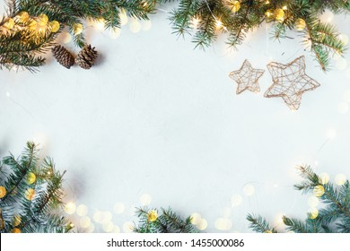 Christmas festive background. Fir branches, garlands, New Year's toys on a wooden background Copy space Top view