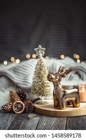 Christmas festive background with toy deer, blurred background with golden lights and candles, festive background on wooden deck table and winter sweater on background