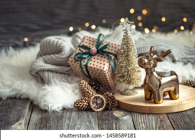 Christmas festive background with toy deer with a gift box, blurred background with golden lights, festive background on wooden deck table and cozy sweater on background