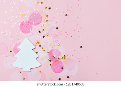 Christmas festive banner background: white christmas tree and confetti with sparcling glitter and stars on pink background. Festive and bright. Copyspace for text. Top view, flat lay.