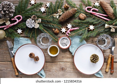 Christmas festive brunch or breakfast table setting. Traditional table decoration with fir branch and cones. Overhead view