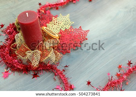 Christmas festive decoration background in red and gold color - big candle with ornate bow and starry red christmas chain on wood background
