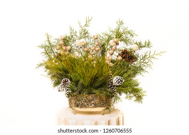 Christmas festive decoration with red baubles, holly with red berries , snow covered pine cones and winter greenery over woodpanel background.
