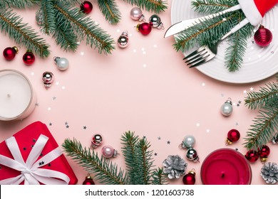 Christmas festive frame with Christmas decorations in red, pink and green colors. Celebration table setting