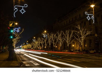 Christmas festive night drive - winter city road with bordering decorated trees and lampposts